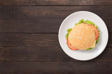 Top view BBQ burger on white dish on wooden background. Copy space for your text. Standard-Bild