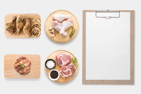 up view: Design concept of mockup clipboard and pork, chicken drumstick on cutting board set isolated on white background. Stock Photo