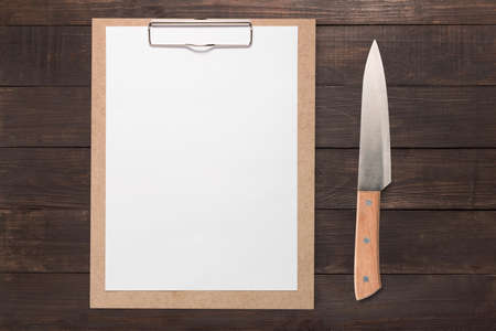 clip board: Clip board and knife set on wooden background. Copy space for your text.
