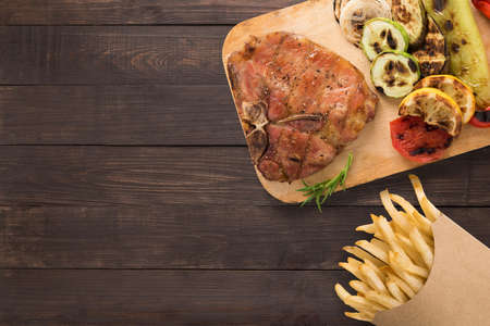 grilled pork chop: Grilled pork chop and chips on the wooden background. Copyspace for your text.