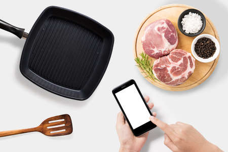 ustensiles de cuisine: Concept of mockup using smartphone and raw pork chop steak, grill pan and spatula set isolated on white background. Clipping Path included on white background. Banque d'images