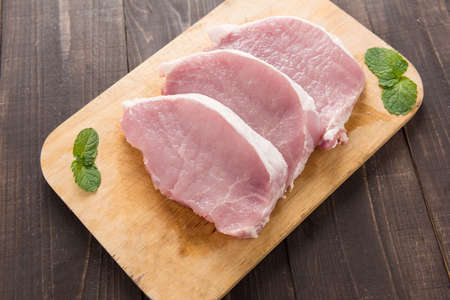 pork: Raw pork on cutting board on wooden background. Stock Photo