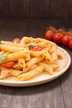 stirred: Penne pasta in tomato sauce with chicken on a wooden table.