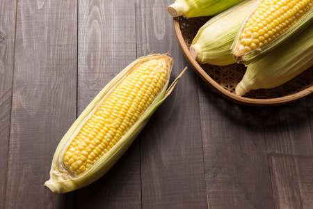 yellow corn: Fresh organic yellow sweet corn on wooden table.