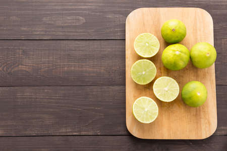 tilted view: Fresh limes on cutting board on wooden background.
