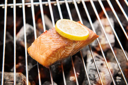 Grilled salmon with lemon on the flaming grill.