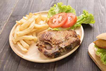 grilled pork chop steak and vegetables with french fries on wooden background. Banco de Imagens