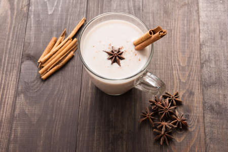 vaso de leche: Masala chai with spices cinnamon, cardamom, ginger, clove and star anise on wooden background. Foto de archivo