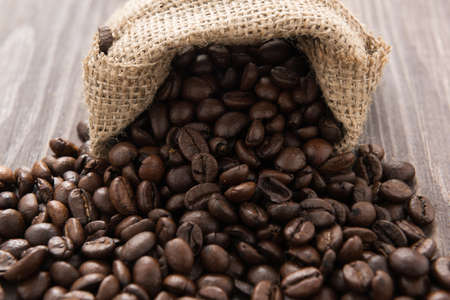 coffee beans in a bag on wooden background. Banco de Imagens