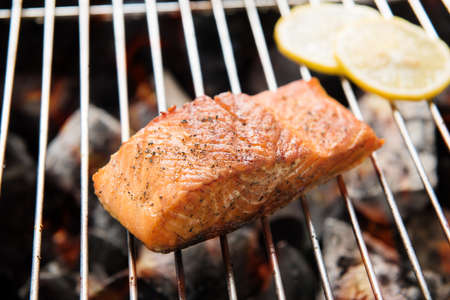 Grilled salmon steaks and lemon on the flaming. Banco de Imagens