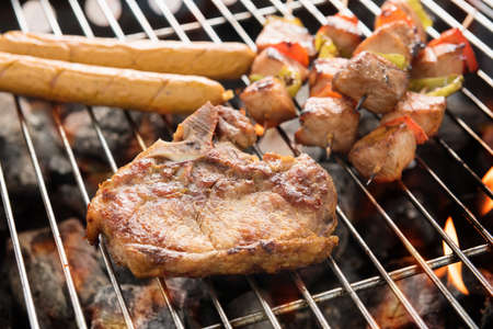 Assorted delicious grilled meat over the coals on a barbecue.