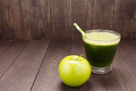 Healthy green smoothie with apple on rustic wood background.
