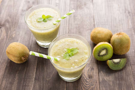 kiwi smoothie with fresh fruits on wooden background. Top view.