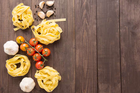 Pasta ingredients. tomato, garlic and pepper on wooden background.