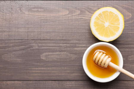 Bowl of sweet honey and lemons on wooden table.