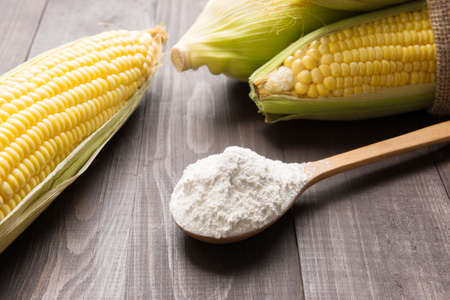 Corn flour and corn on wooden table.