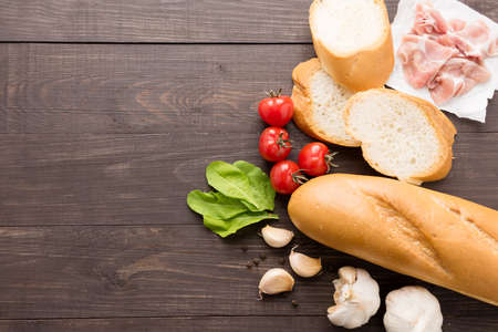 Ingredients for sandwich with smoked meat, baguette on wooden background.