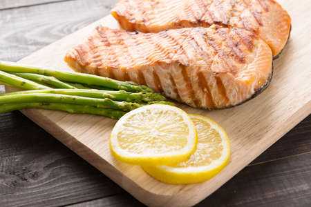 Grilled salmon with lemon, asparagus on the wooden table. Banco de Imagens