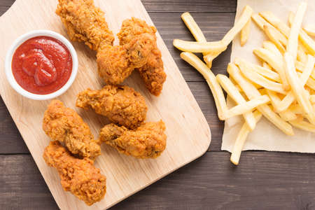 fried chicken drumstick and french fries on wooden background. Banco de Imagens