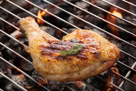 Grilled chicken leg over flames on a barbecue.