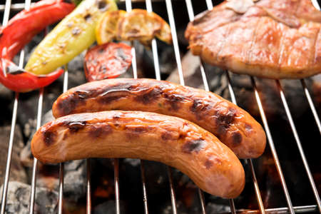 Sausages and grilled vegetables on the grill close up.