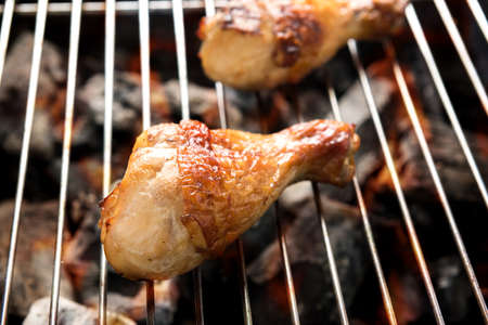 Grilled chicken drumstick over flames on a barbecue.