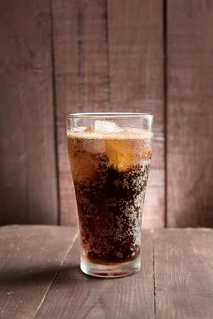 Cola in glass with ice on wooden background. Banco de Imagens