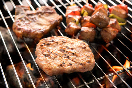 Assorted delicious grilled meat over the coals on a barbecue Banco de Imagens