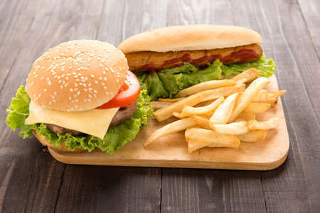 Hot dogs, hamburgers and french fries on the wooden background.