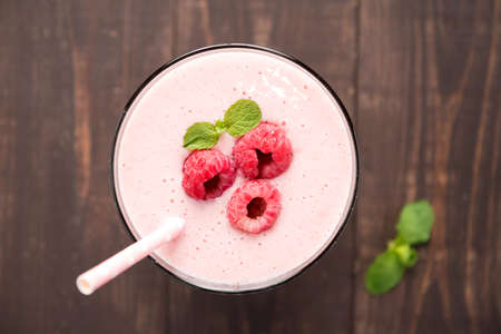 Raspberry fruit smoothie with straw on wooden background Banco de Imagens