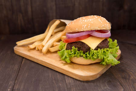 Cheeseburger with french fries on wooden background. Banco de Imagens