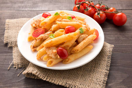 Penne pasta in tomato sauce with chicken on a wooden table.