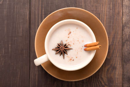 Masala chai with spices cinnamon , cardamom, ginger, clove and star anise on wooden background.