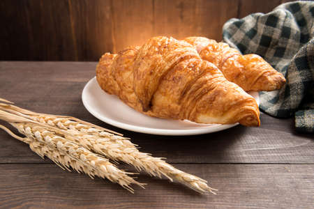 The breakfast croissant on the wooden table.