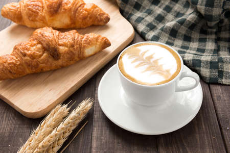 Breakfast coffee cup and croissant on wooden table. Banco de Imagens