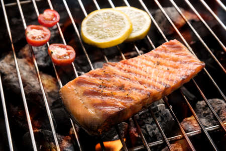 Grilled salmon with lemon on the flaming. Banco de Imagens