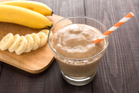 Banana smoothie and fresh banana on wooden background. Banco de Imagens