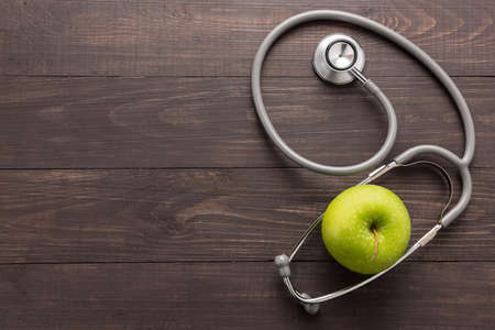 Concept for healthcare, Stethoscope and green apple on wooden background.