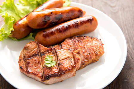 Grilled meat, sausages and vegetables on dish close up.