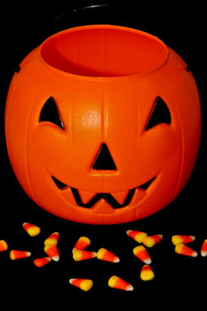 Plastic pumpkin with candy corn in front of it photo