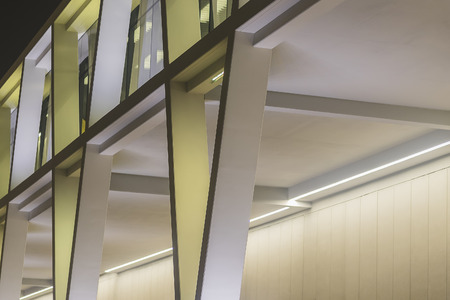 Yellow and White Modern Lit Building At Night With An Angle View Imagens