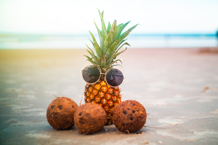 Fun Pineapple and Coconuts Wearing Sunglasses Enjoying Relaxing Day At The Ocean