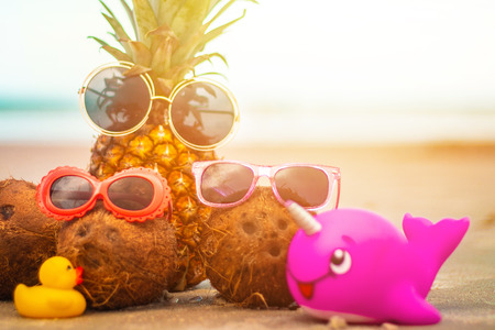 Adorable Pineapple and Coconuts Wearing Sunglasses On Sunny Tropical Beach