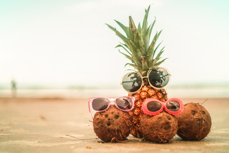 Pineapple and Coconuts Wearing Sunglasses On Sandy Beautiful Beach Imagens