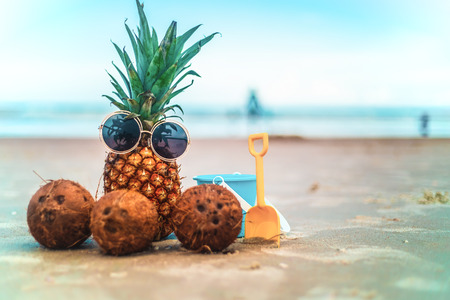 Cute Pineapple Wearing Sunglasses and Coconuts Relaxing On Sunny Beach