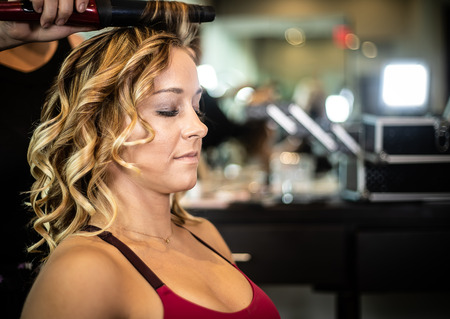 Young Beautiful Female Getting Hair Styled and Curled Imagens
