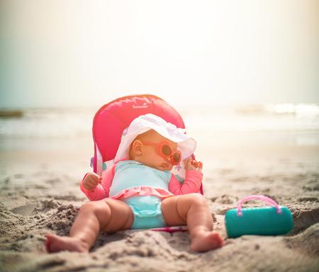 Cute Baby Girl Wearing Sunglasses Sleeping On A Sunny Beach