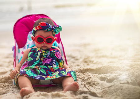 Adorable Baby Girl Wearing Sunglasses and Headband Sitting On A Carribean Beach Imagens