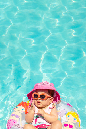Beautiful Baby Girl Wearing Hat and Sunglasses On A Float In Clear Water Imagens