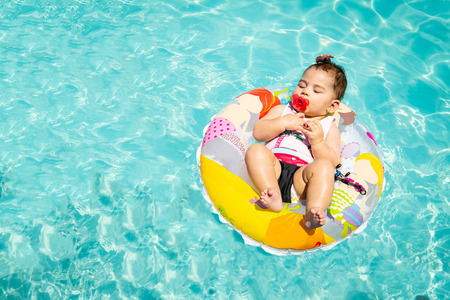 Adorable Baby Girl Floating On Blue Water During Sunny Day